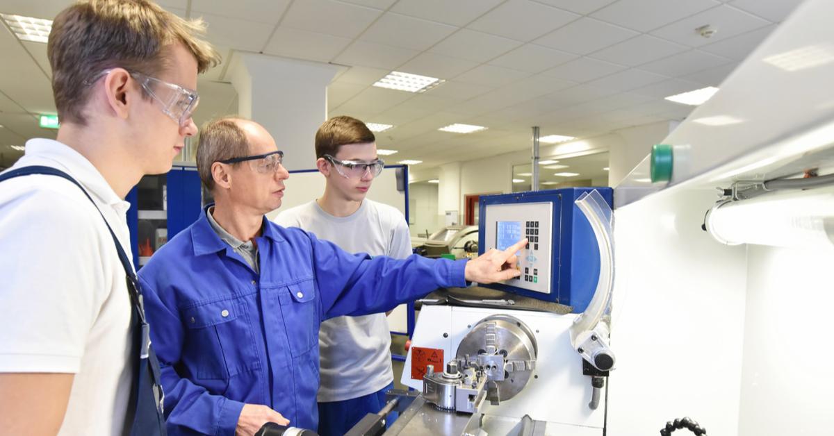 Formatore mostra a due apprendisti come operare un macchinario