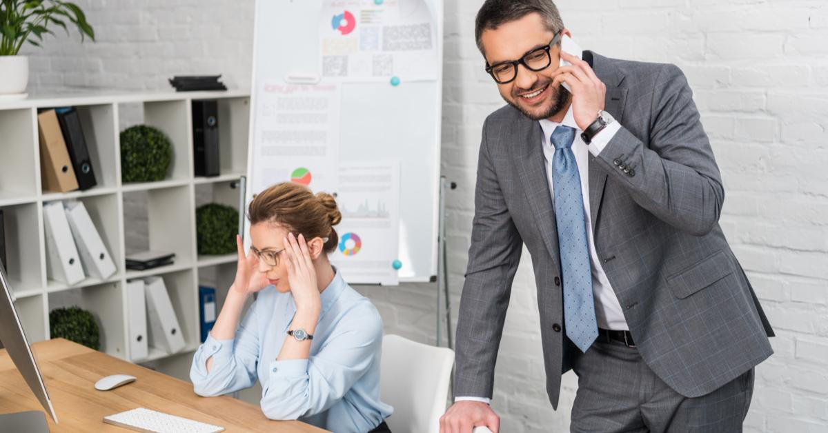 impiegato d'ufficio parla al telefono disturbando la sua collega che sta cercando di lavorare