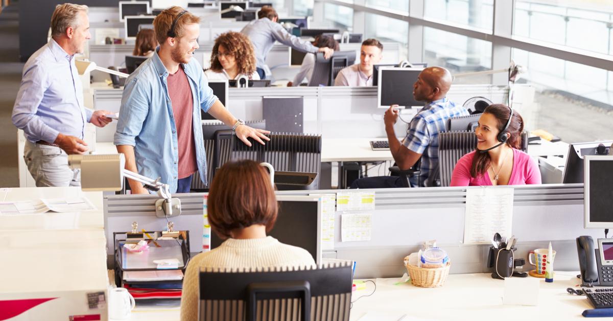Colleghi lavorano in ufficio open space, alcuni di loro chiacchierano