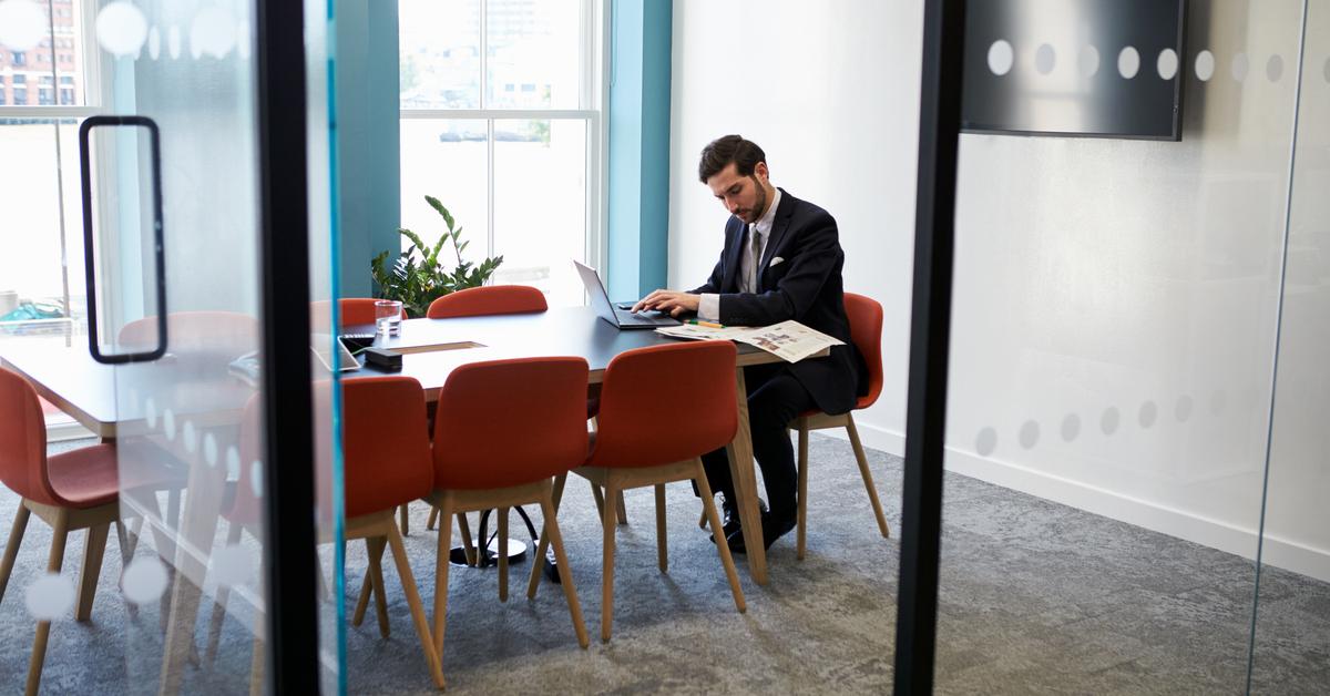 Impiegato lavora da solo in una sala conferenza vuota